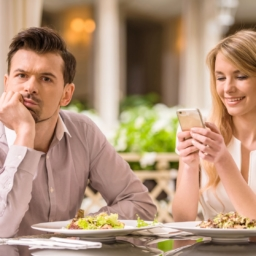 man annoyed with woman distracted by phone on date night