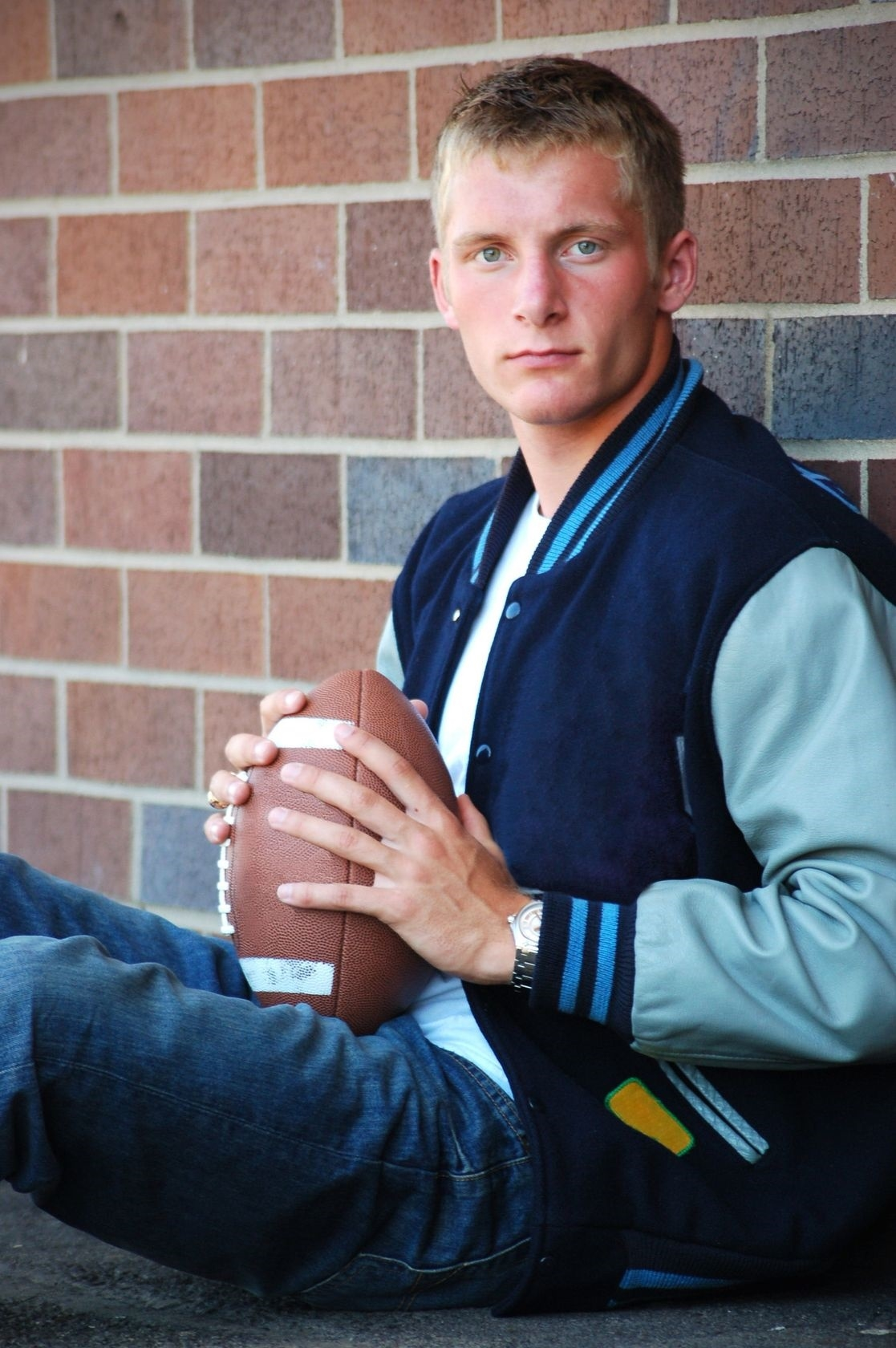 guy wearing a varsity jacket and holding a football