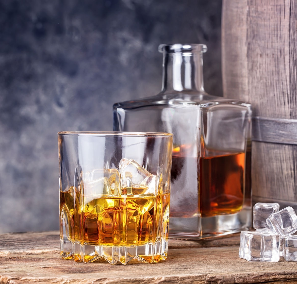 whisky in glass and ice on the background of wooden barrels