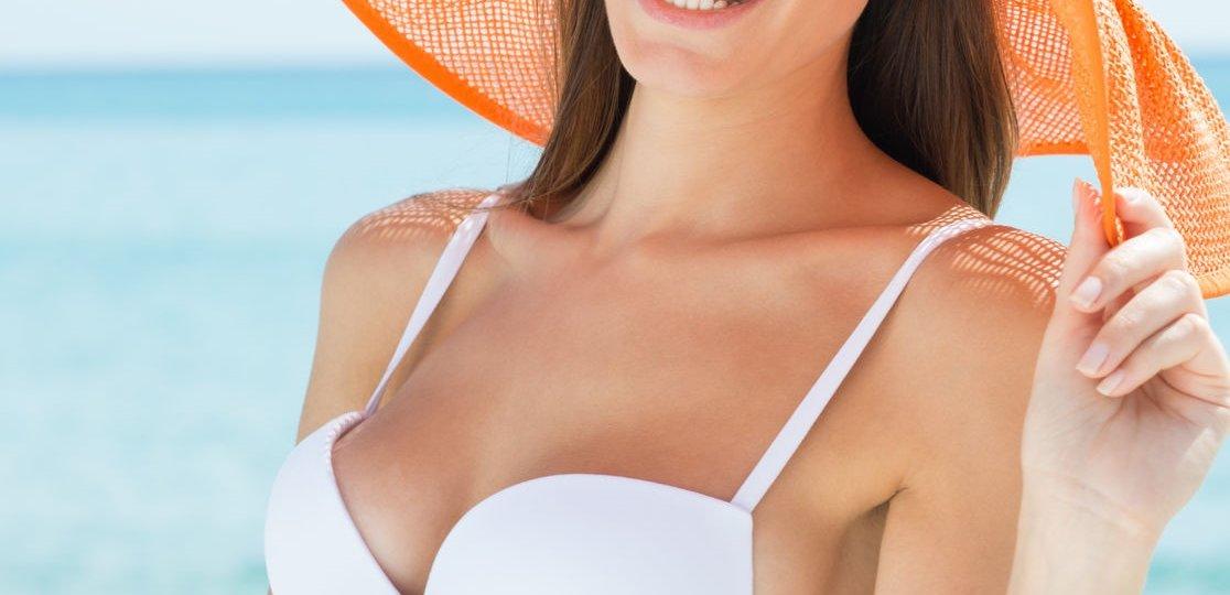 woman in white bikini and orange sun hat being safe in the sun