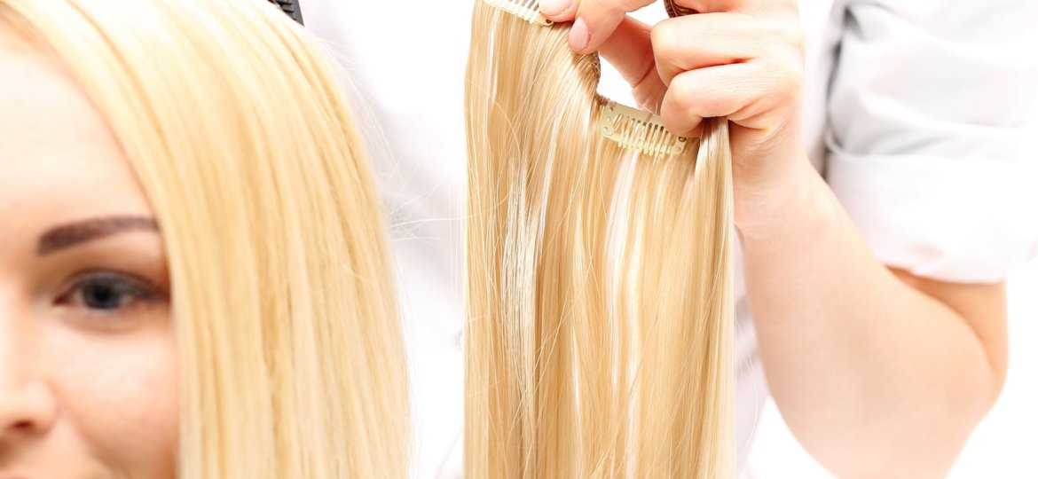 girl at a salon getting blonde hair extensions