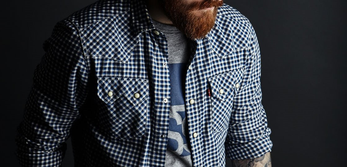 pensive red bearded handsome stylish man in blue gingham print checkered shirt, studio portrait on dark background