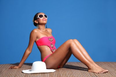 long legged young african american woman wearing pink monokini swimsuit sitting on bamboo mat sun tanning with head back and eyes closed. sun hat and sunglasses nearby.