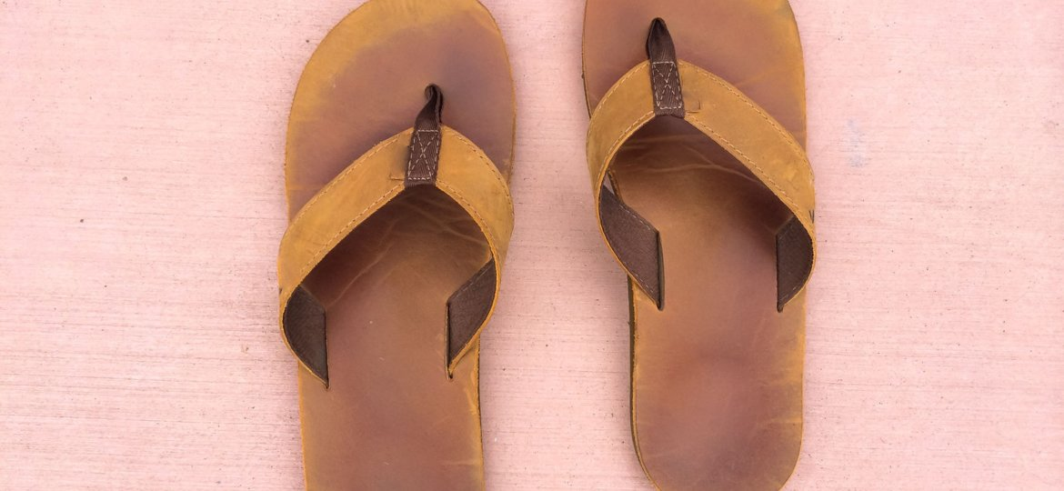 sandals with no feet on the ground that are quite worn and old but in good condition for this type of leather footwear.