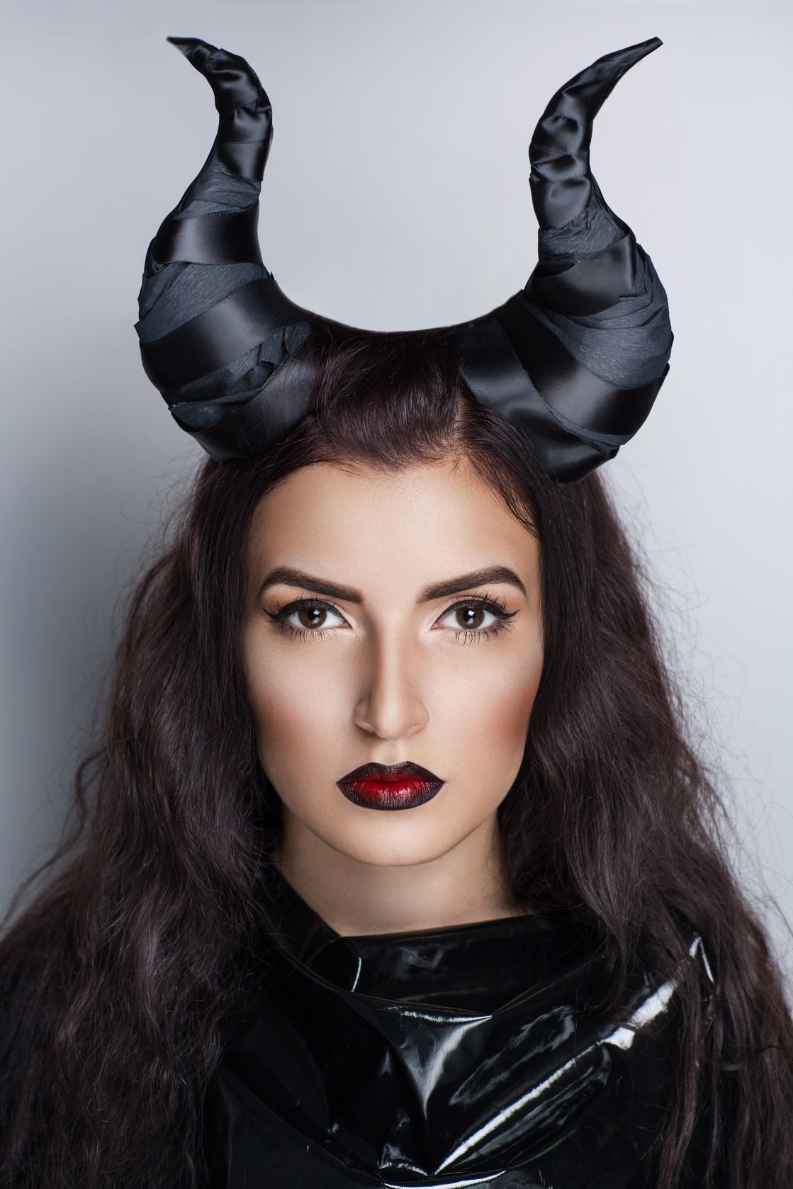 model wearing perfect makeup beautiful face, tanned soft skin dark red lips, long combed hair, huge halloween devil horns decorates her head