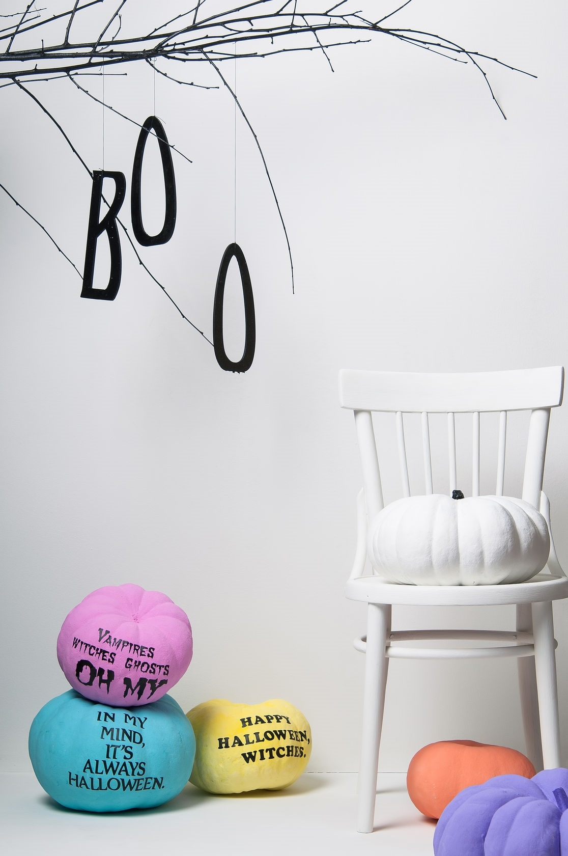 halloween pumpkins with brightly colored chair and tree on a white background