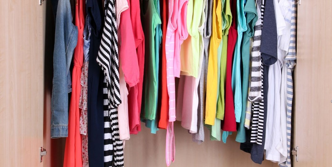 colorful clothes organized and hanging in wardrobe