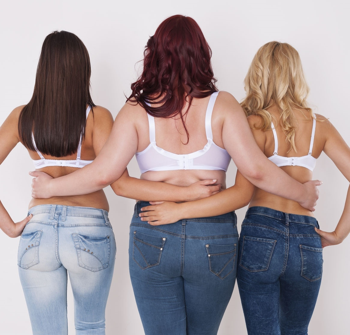 three woman showing their back to the camera wearing only their bra and jeans