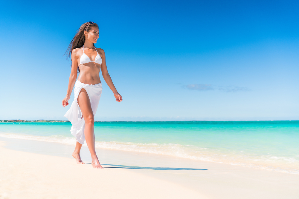 Woman walking down beach coastline with waist cover up
