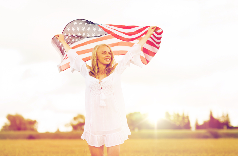 Girl in white cover up with an American Flag in the air