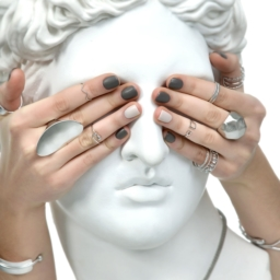 girl's hands wearing midi-rings covering statue's eyes