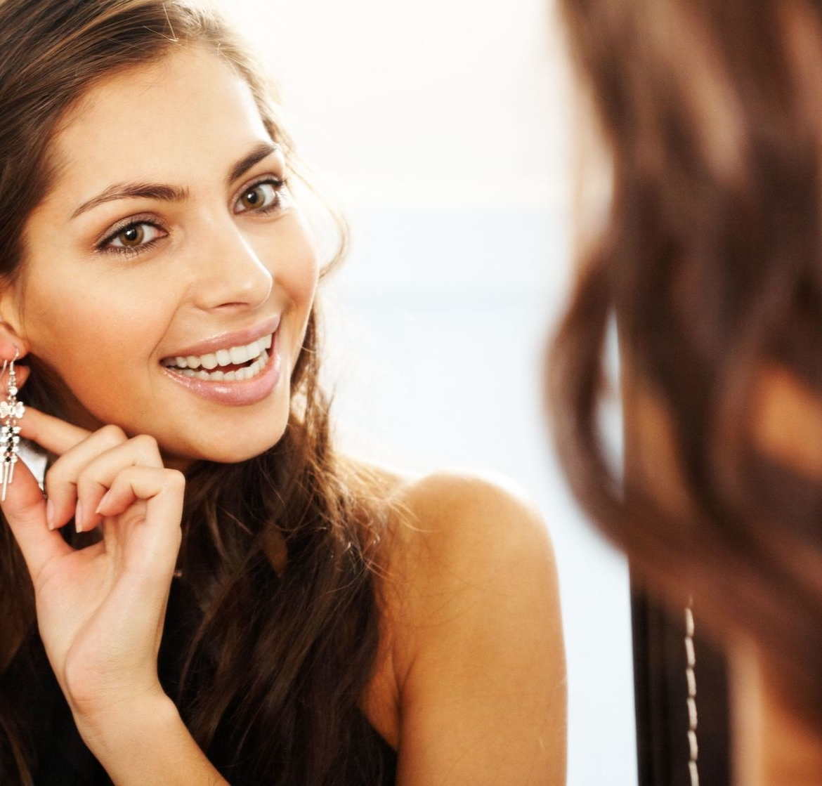 image of pretty female looking in mirror and putting on mis-matched earrings