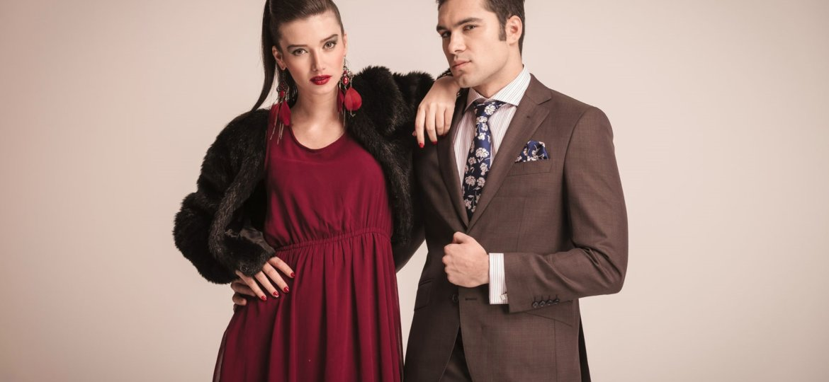 fashion model wearing burgundy and holding her arm on her lovers shoulder while he is fixing his jacket.