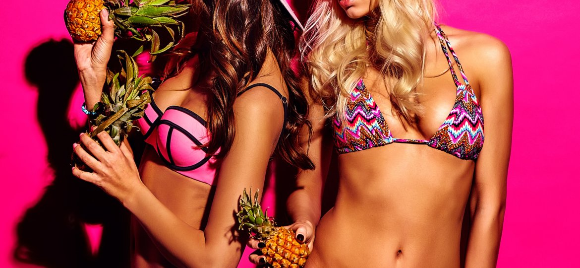 two models wearing bikinis and backwards hats and posing on a pink background