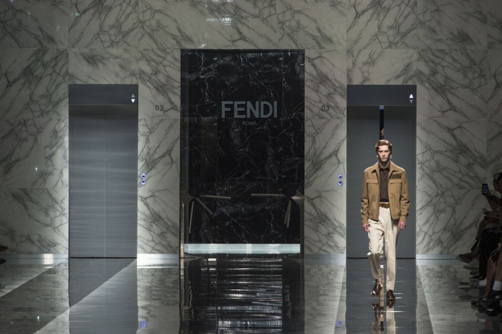 Male model walking down shiny hallway with Fendi displayed behind him.