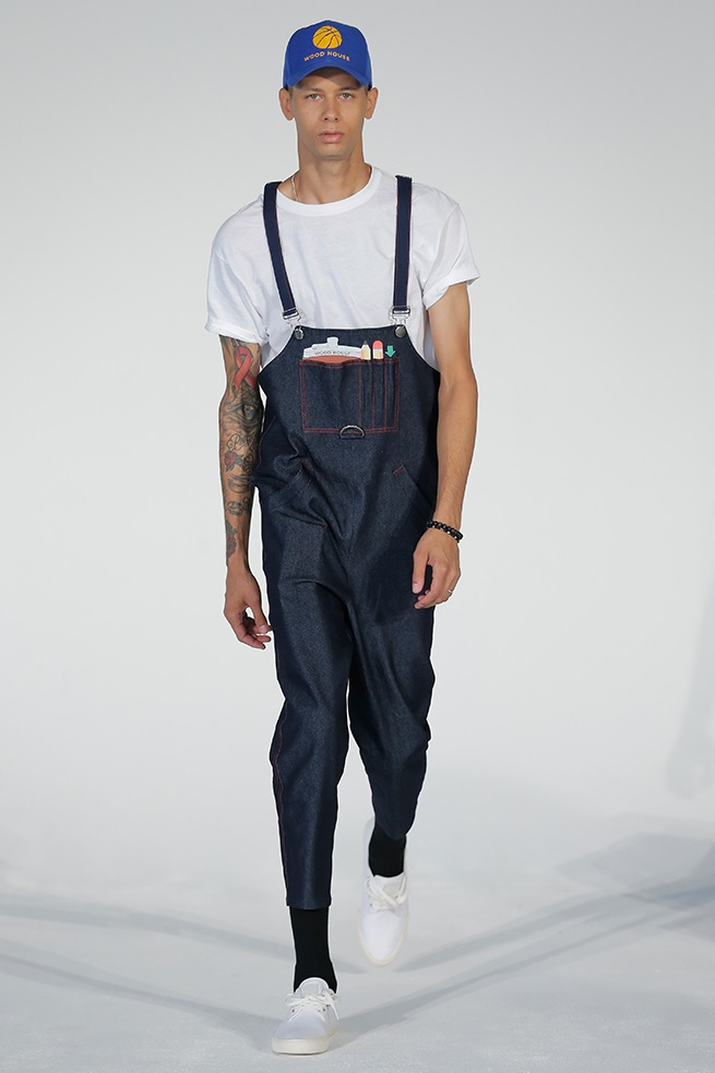 Man in low cut overalls with hat and white t shirt