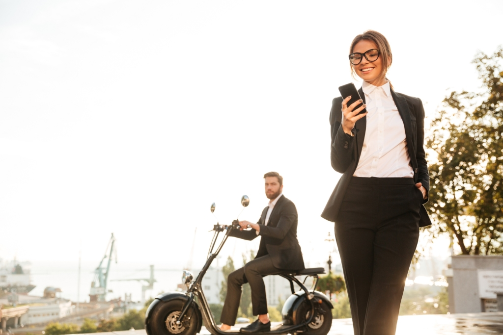 Confident business woman in suit and business man on bike