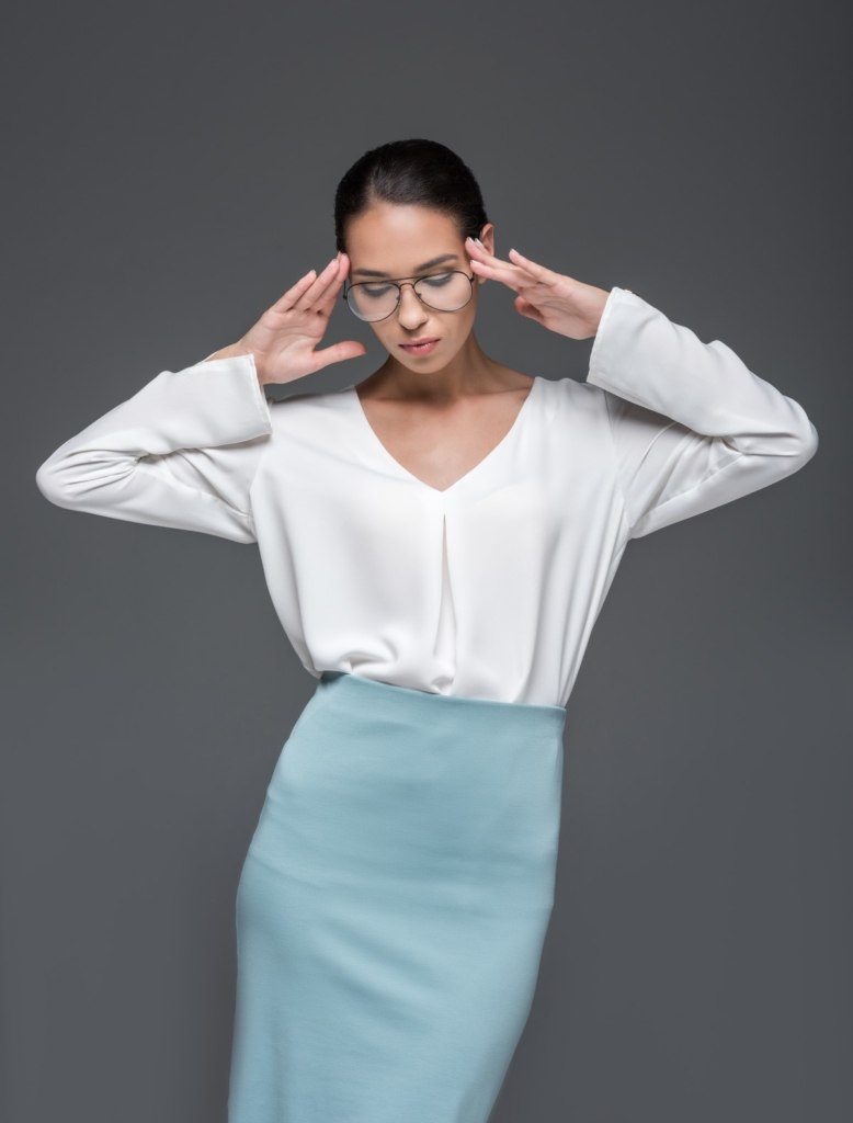 Model wearing a loose white blouse and a pale blue pencil skirt
